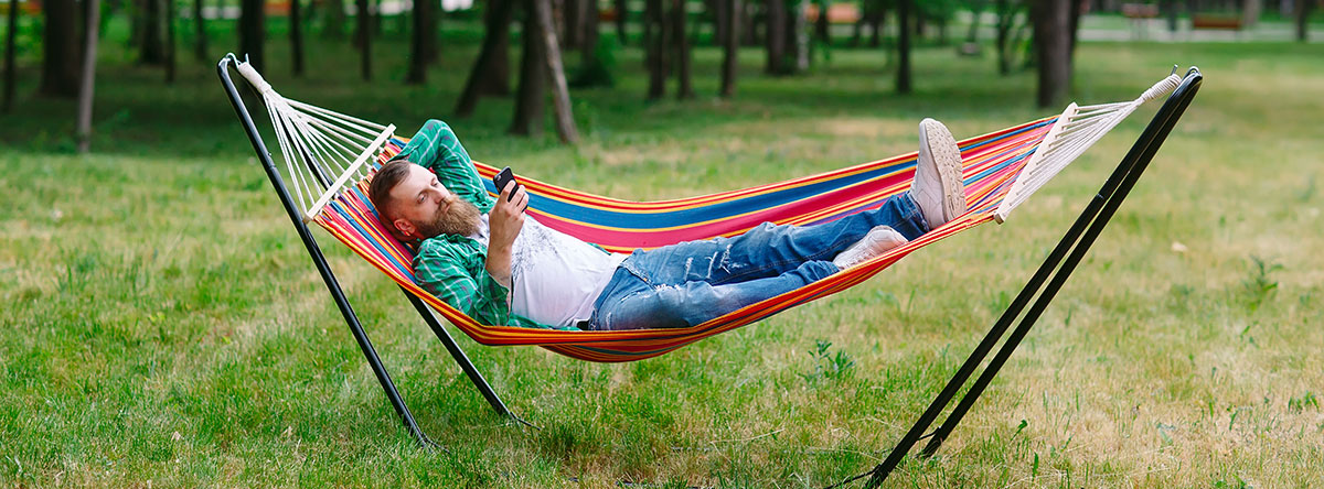 Man Lounging in Hammock Outside & Reading Phone - SEO Content Blog