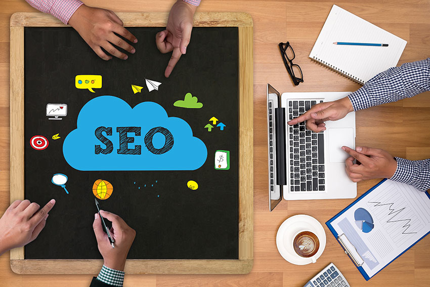 Workers Around Chalkboard & Laptop Working on SEO Content - DMG Blog