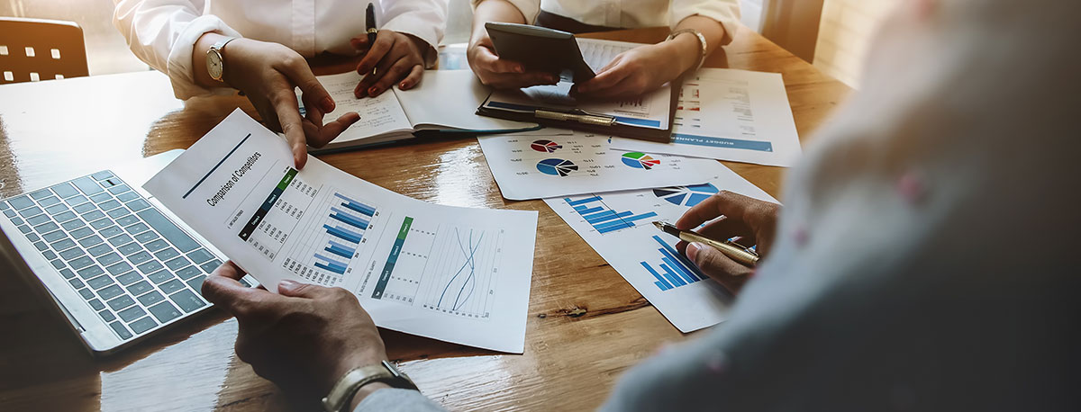 3 business professionals sitting around a table looking over analytics spreadsheets and laptop - SEO Strategy Blog