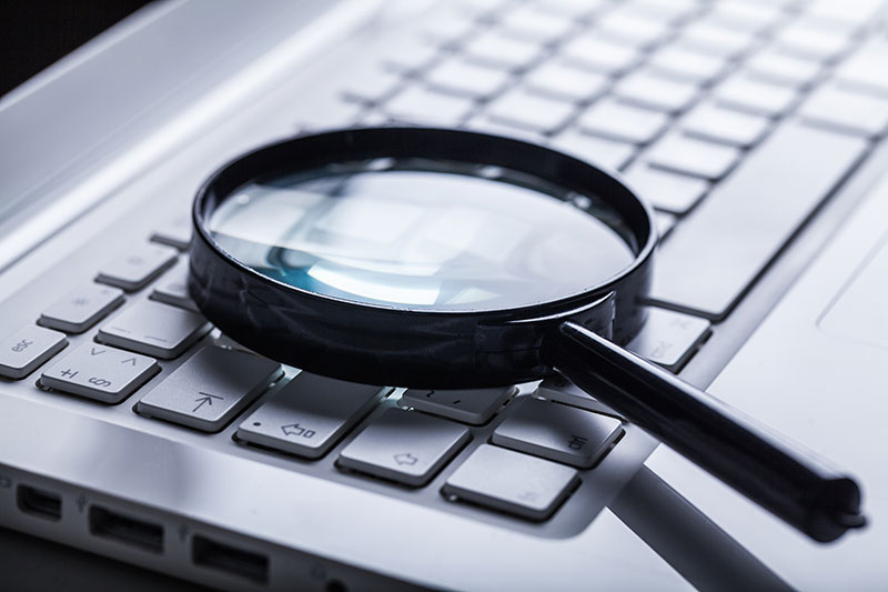 Magnify glass laying on a laptop keyboard - SEO Strategy Blog
